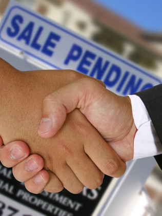 A home buyer shaking hands with a real estate lawyer in New York, NY